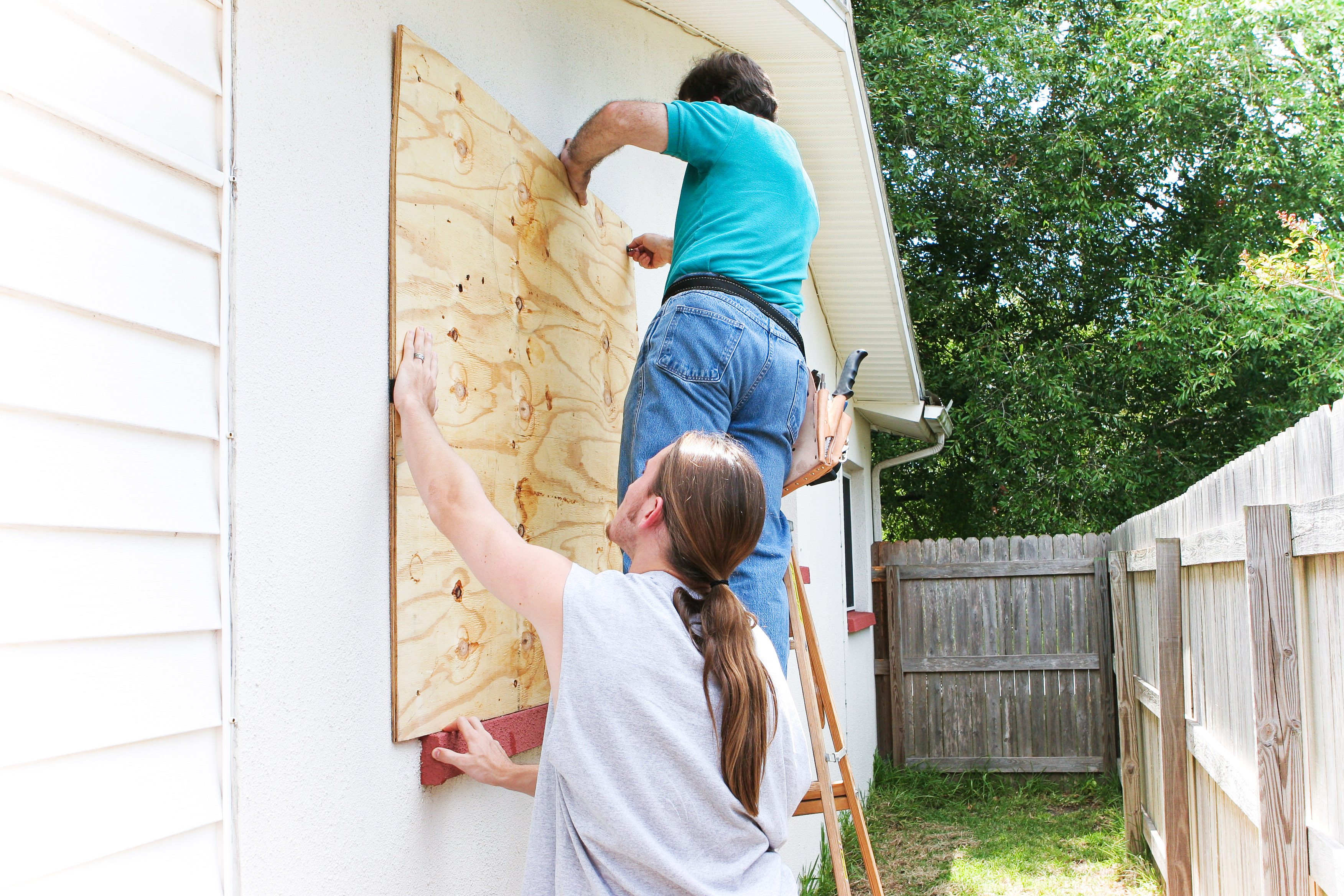 Filho adolescente ajudando seu pai a tapar as janelas - editado