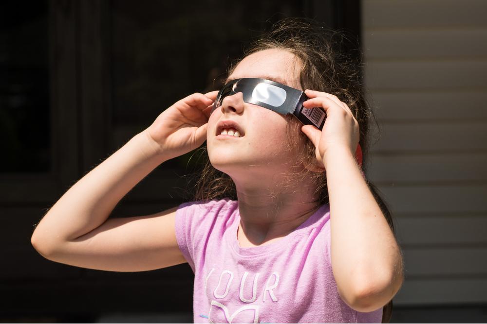 فتاة صغيرة تنظر إلى كسوف الشمس