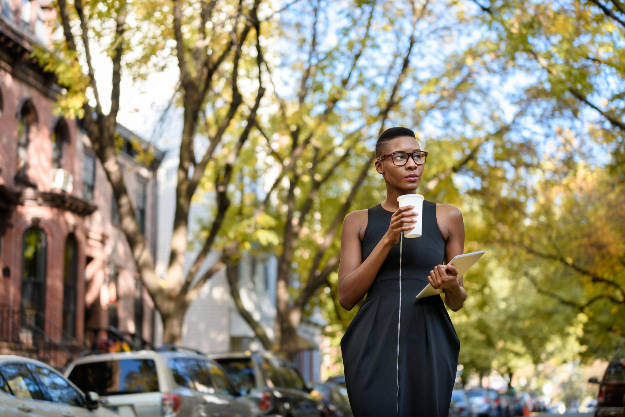 Jovem mulher de negócios na África andando na rua.72ppi