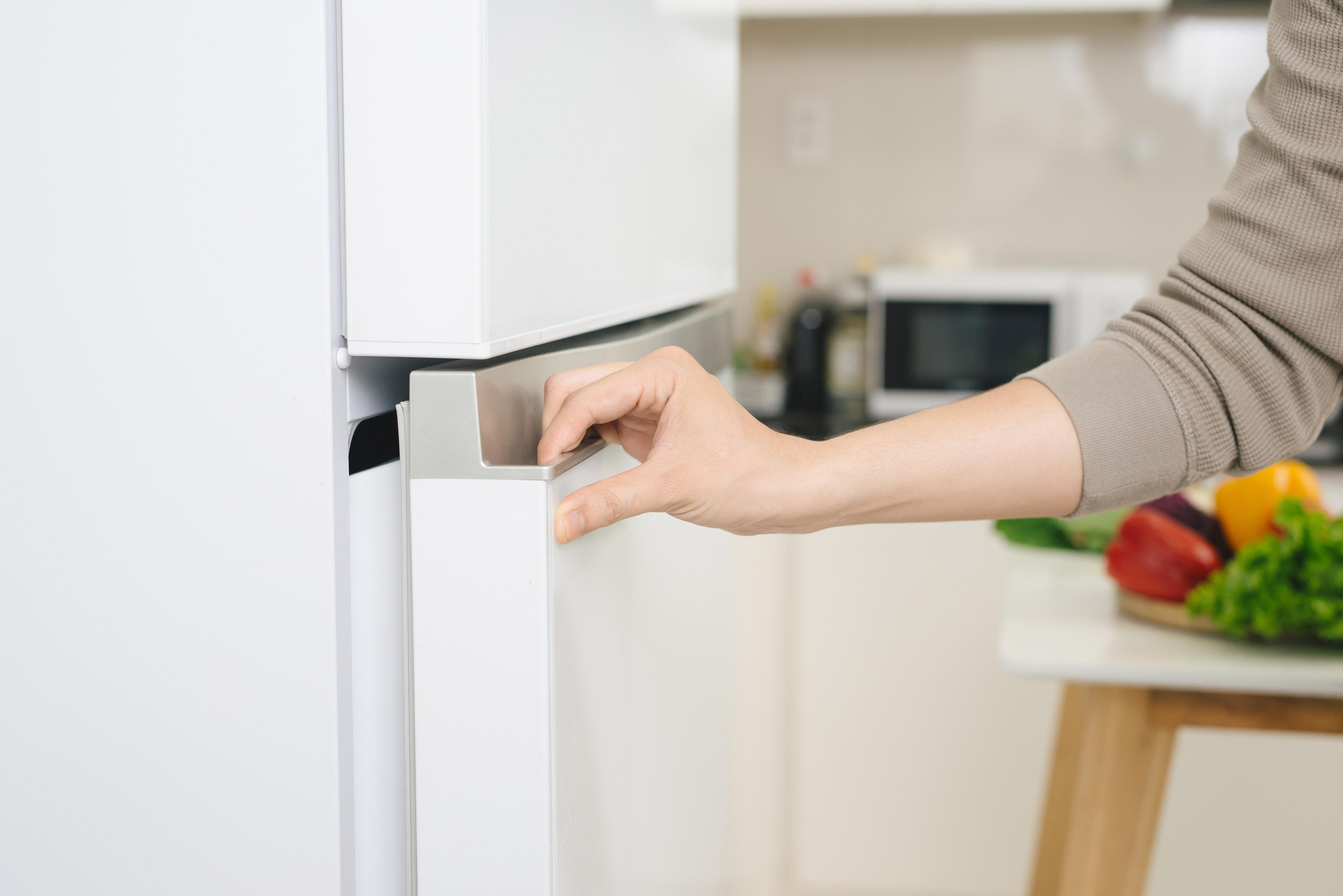Mão masculina está abrindo a porta da geladeira branca - editado