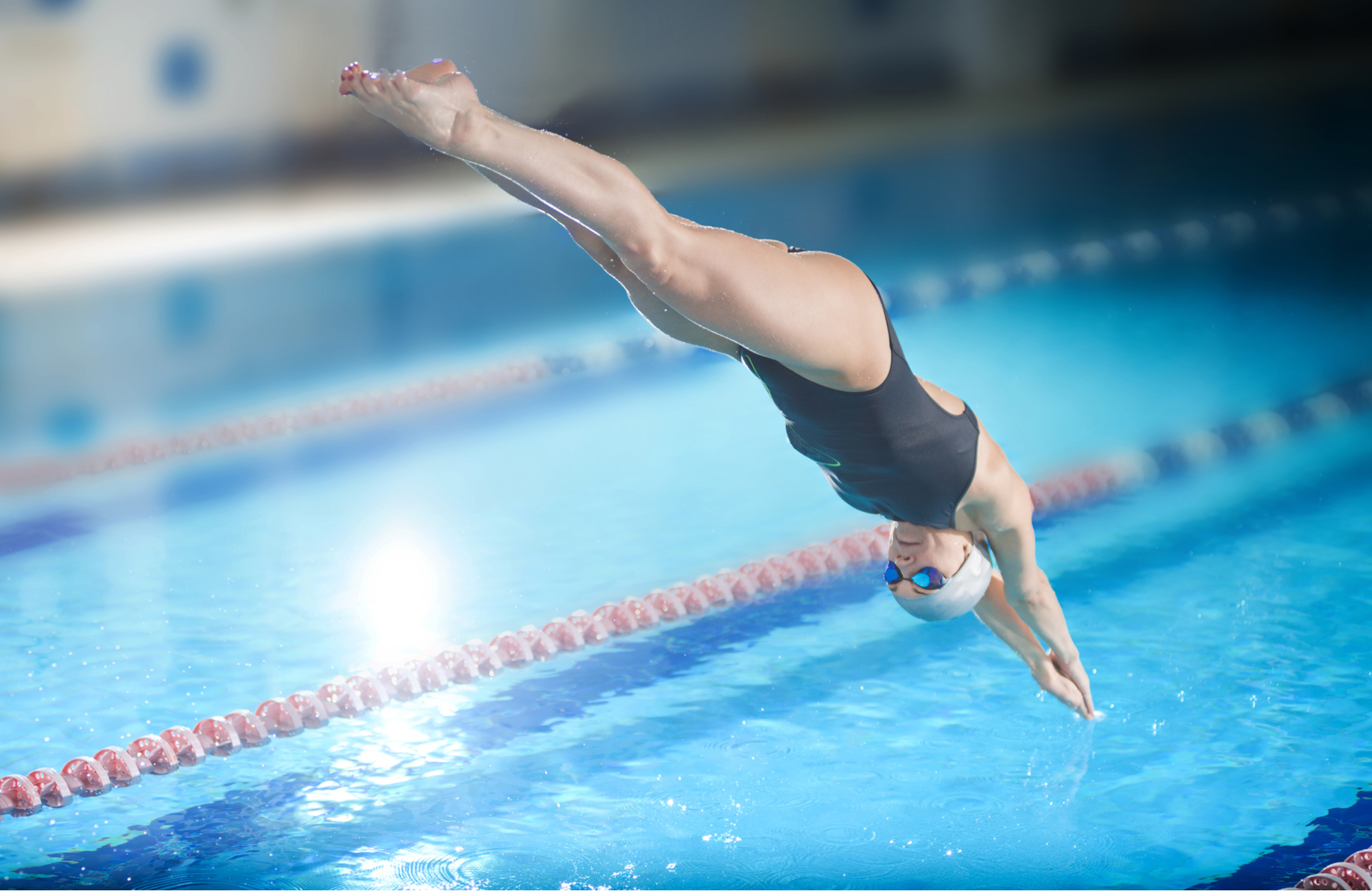 Female swimmer jumping and diving into indoor swimming pool