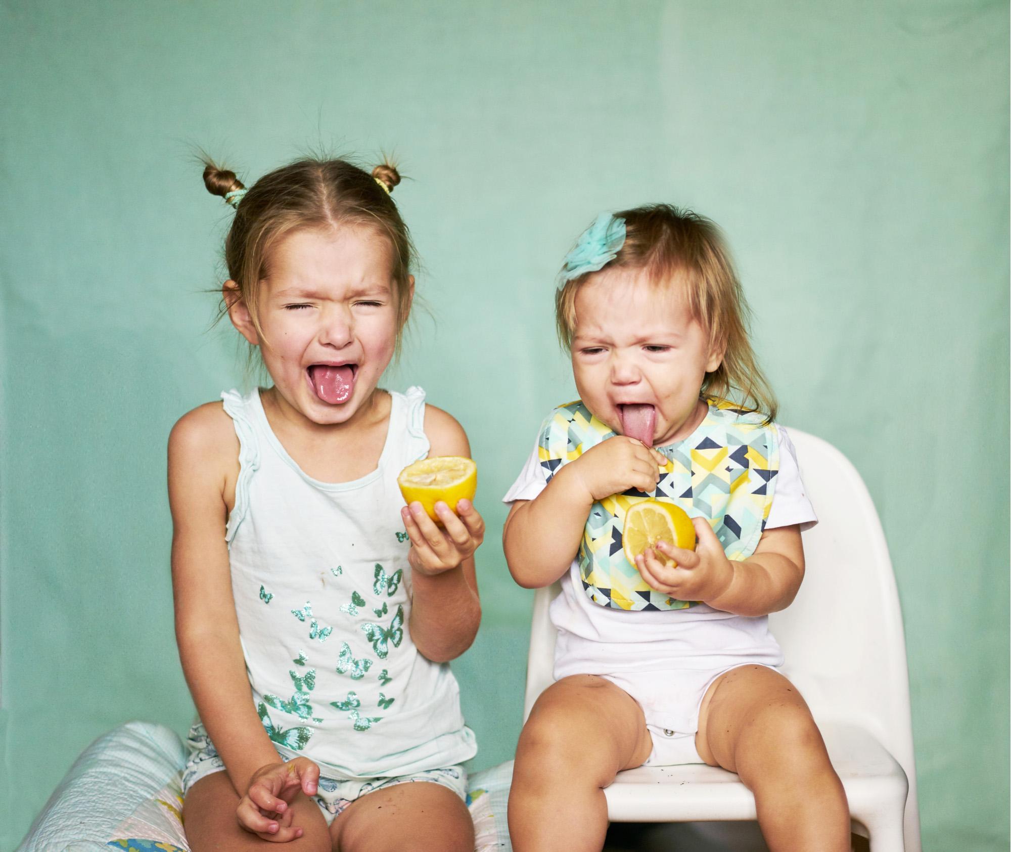 فتاتان تتذوقان الليمون الحامض
