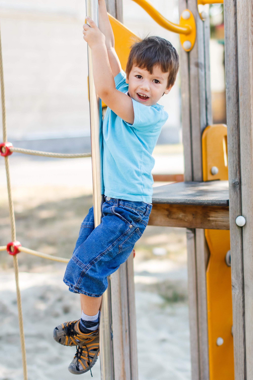 ولد ينزلق لأسفل على عمود في حديقة