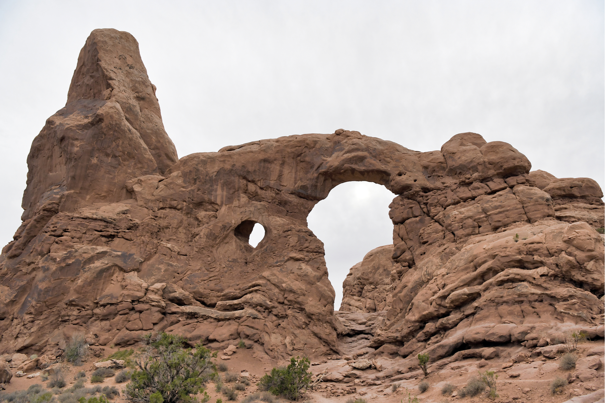 Close-set pair of natural arches known as a pothole arch formed by erosion (nature).
