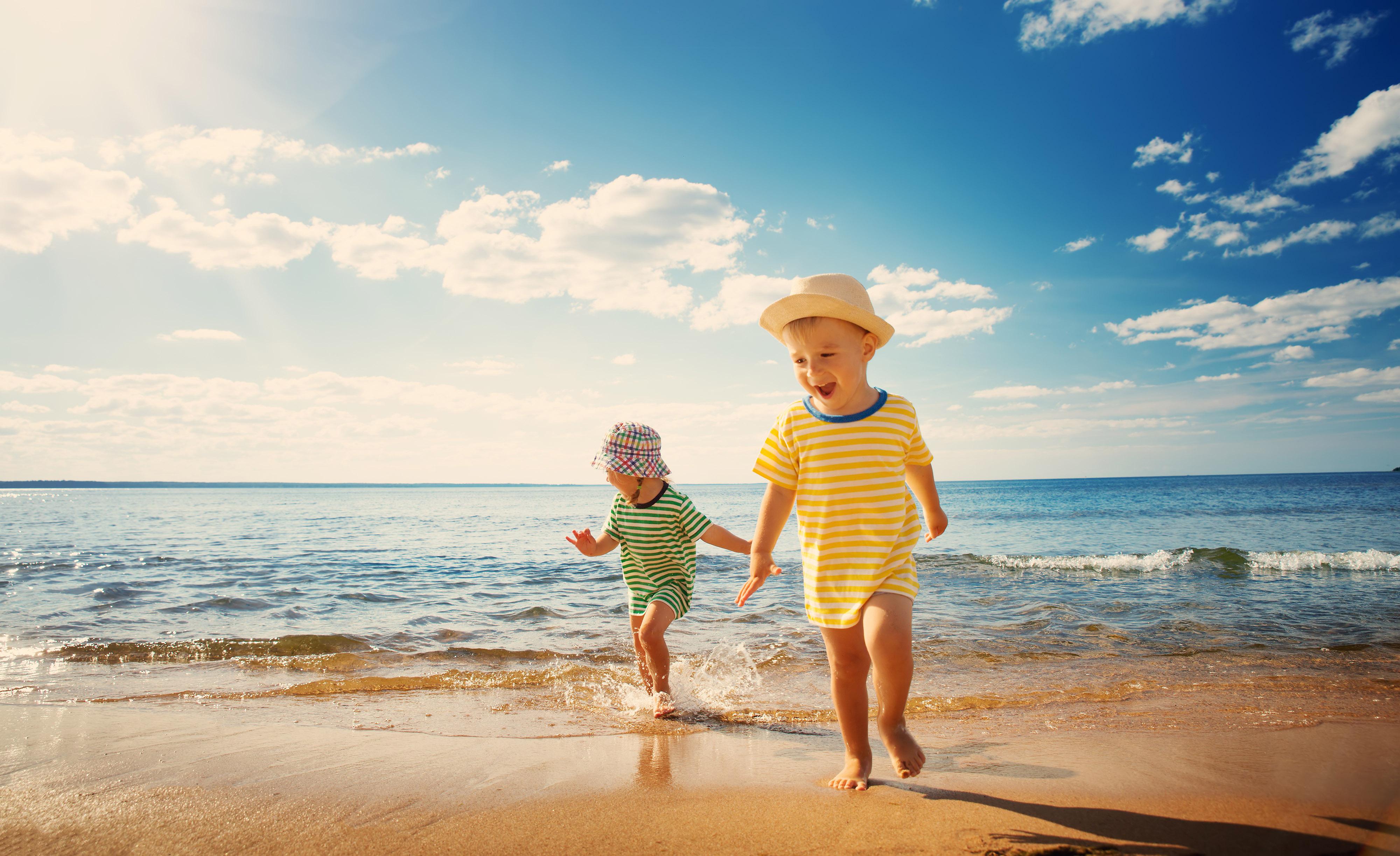 Menino e menina brincando na praia - editado