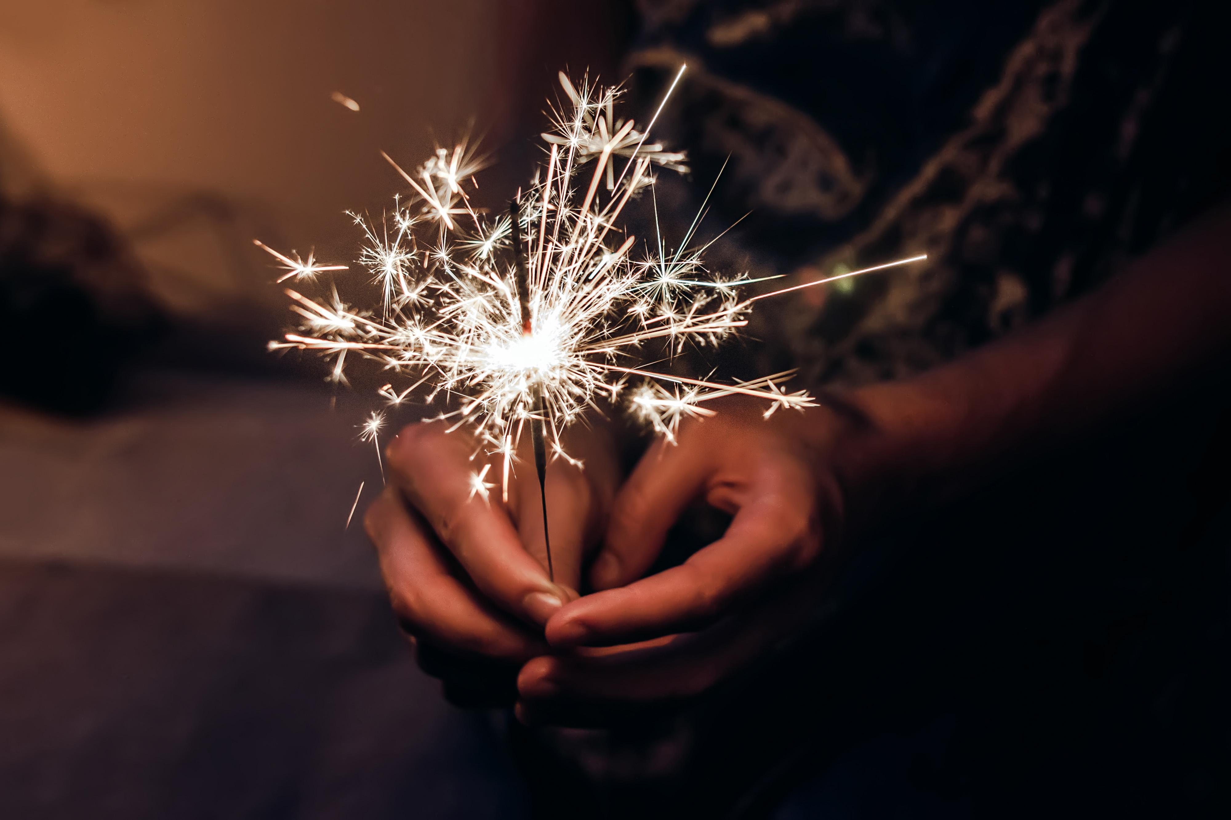 Hand holding a burning sparkler firework bengal light-72 ppi
