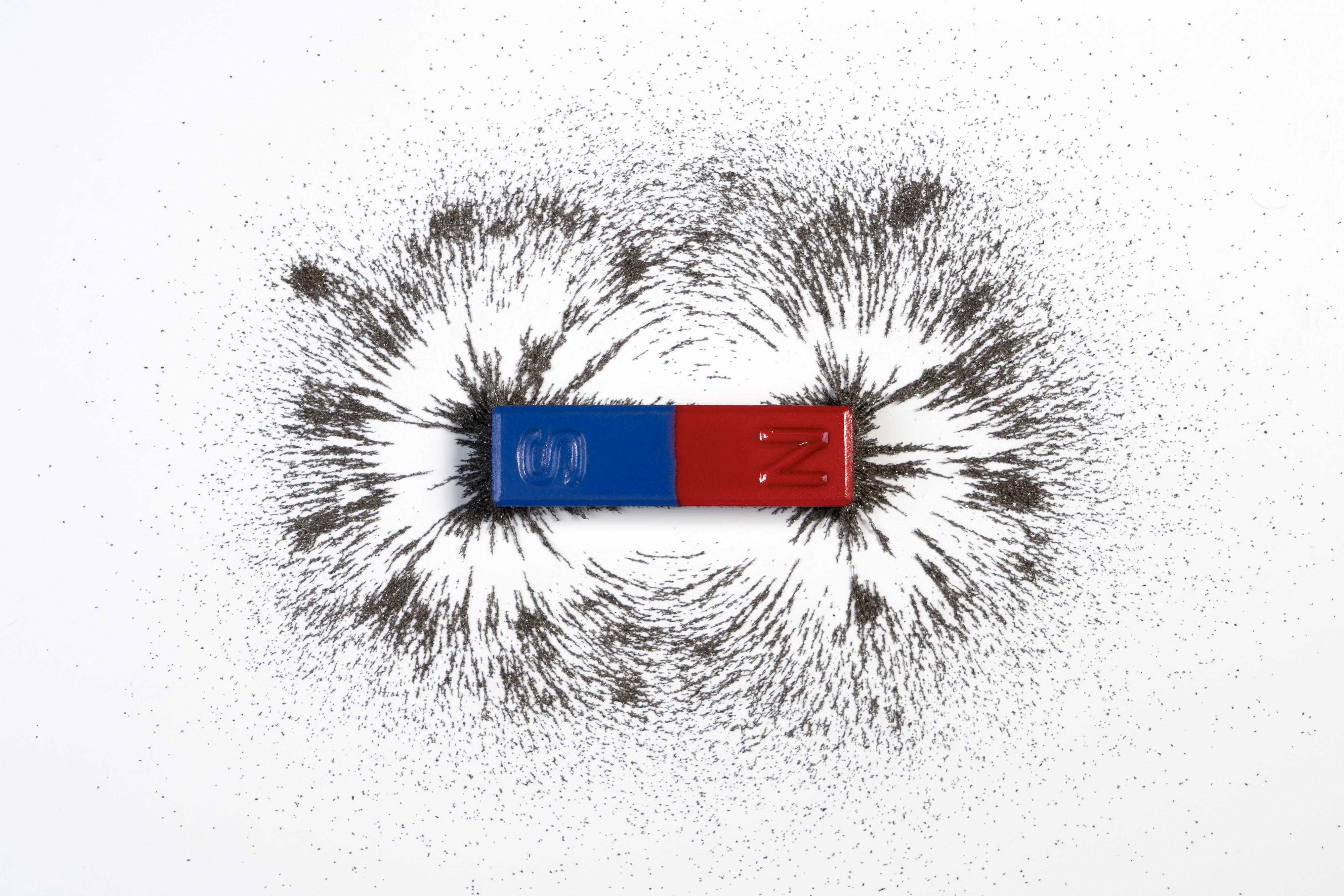 شكل المجال المغناطيسي لقضيب مغناطيسي ذي قطبين أحدهما لونه أحمر والآخر لونه أزرق أو مغناطيس منثور حوله برادة حديد – مُعدَّل
