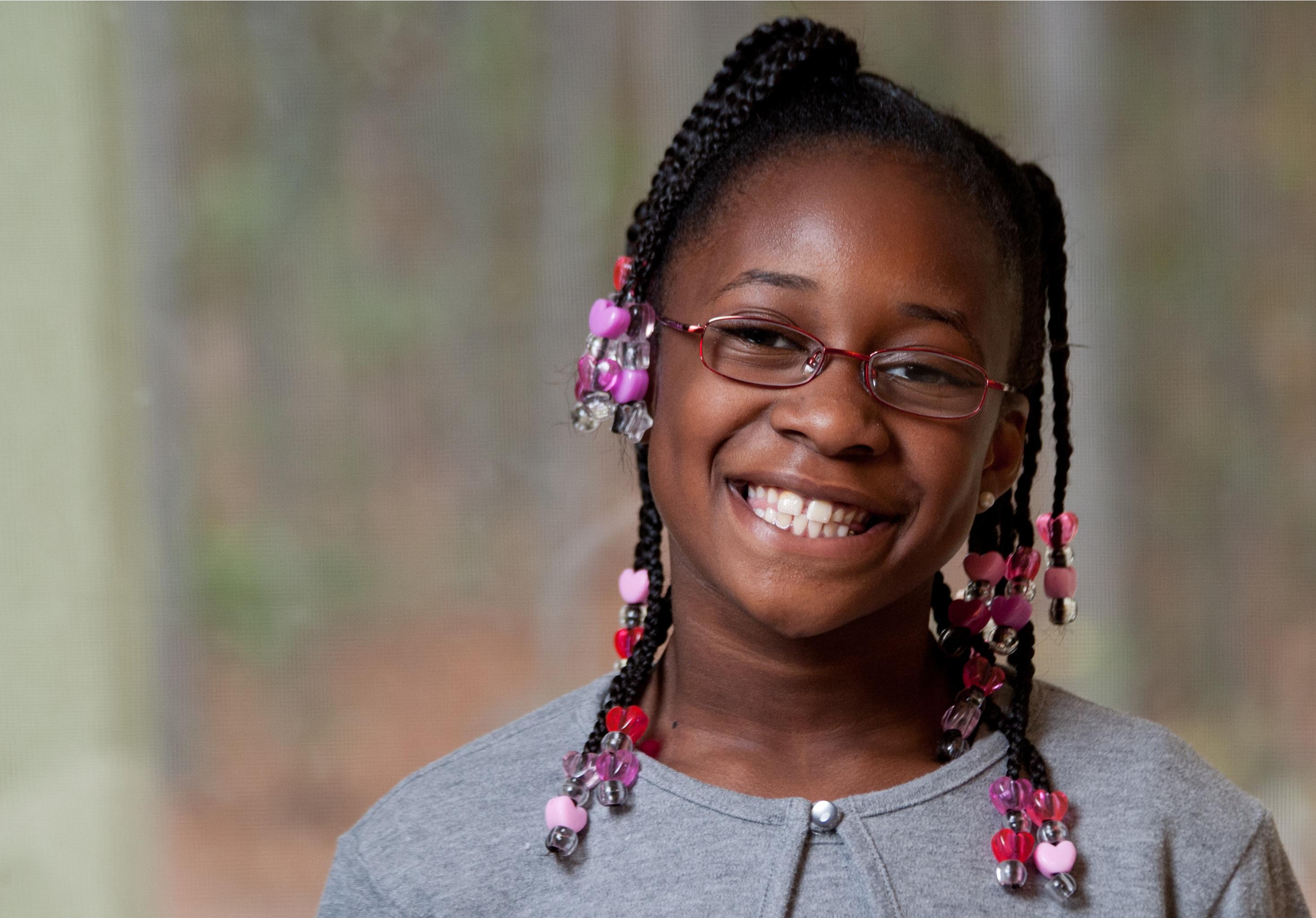 Uma menina negra feliz sorrindo.