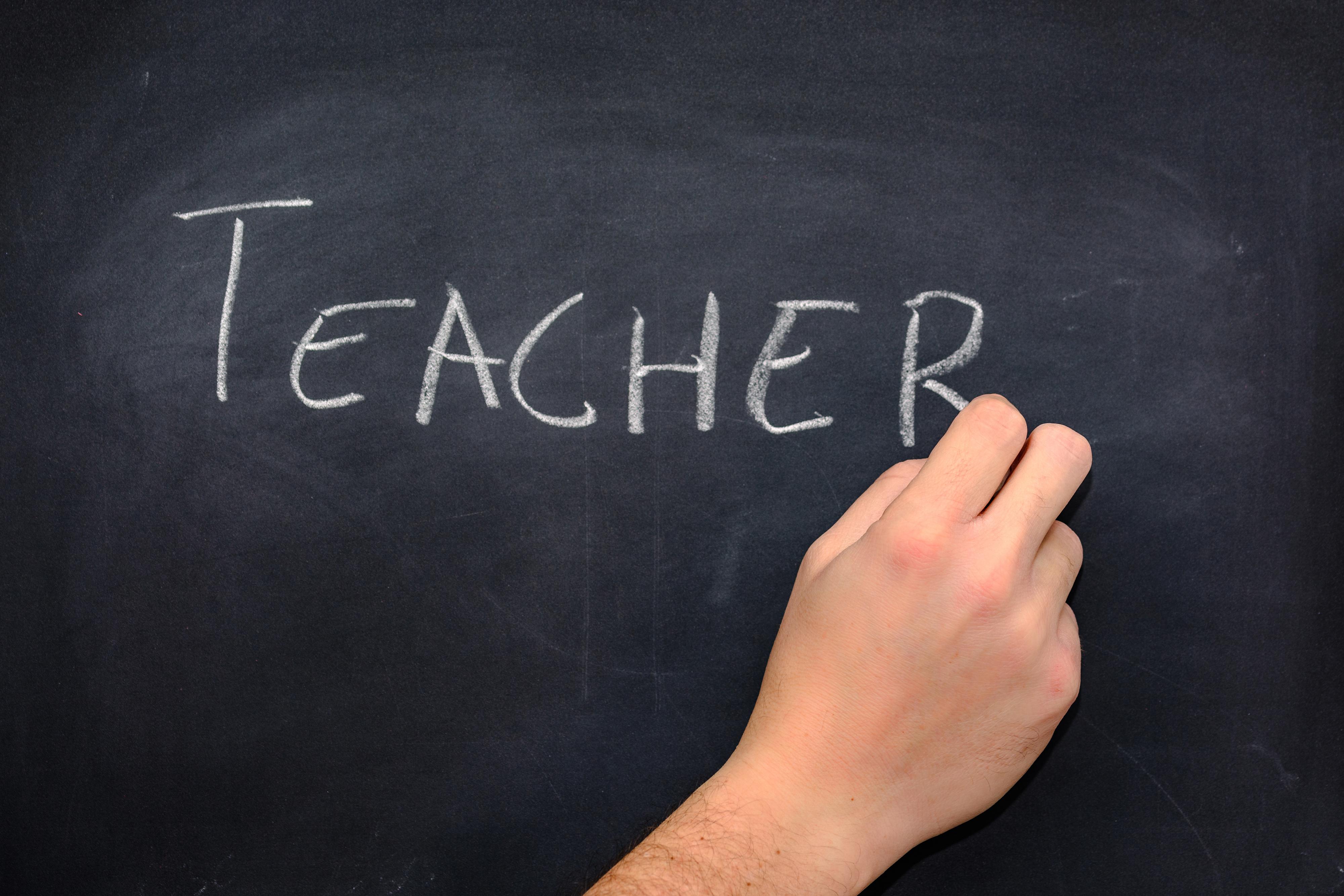 Mão de um professor escrevendo a palavra professor em um quadro negro