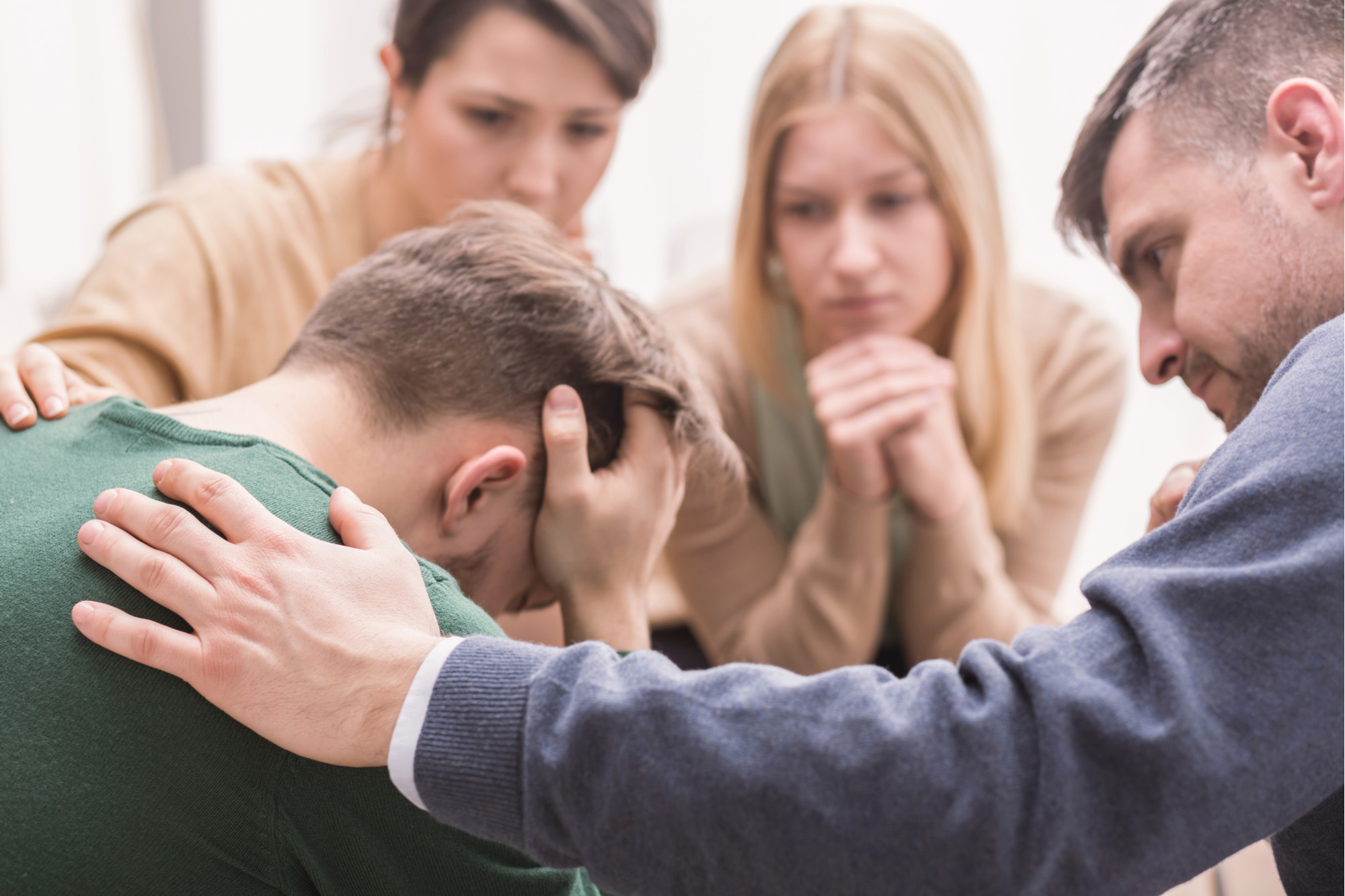 Close-up of a devastated young man holding his head in his hands and friends supporting him during group therapy - 72 ppi
