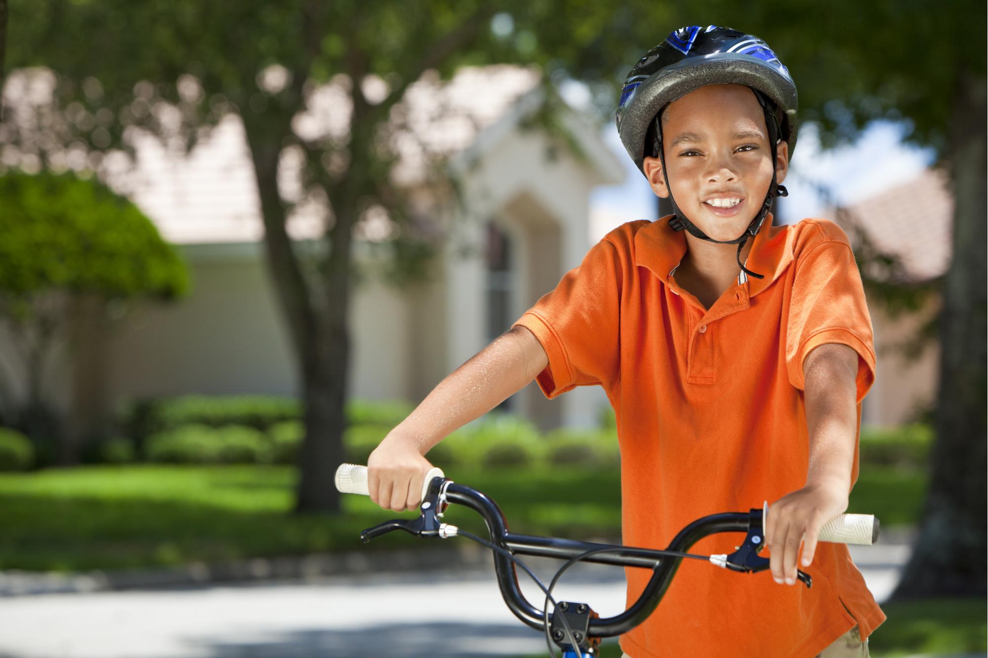 Um jovem menino afro-americano andando de bicicleta ou bicicleta no verão